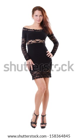 Pretty young woman is standing and looking at the camera. She is wearing a black cocktail dress decorated with lace. - stock photo