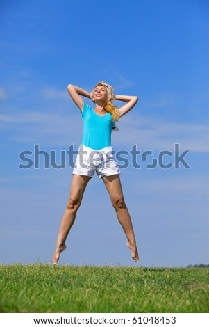 pretty young woman jumping on green grass against brightly dark blue sky