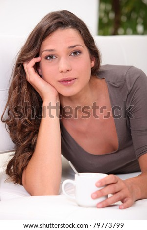 Pretty young woman laid with cup of coffee