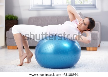 Pretty young woman laying on fit ball, doing workout, smiling. - stock photo