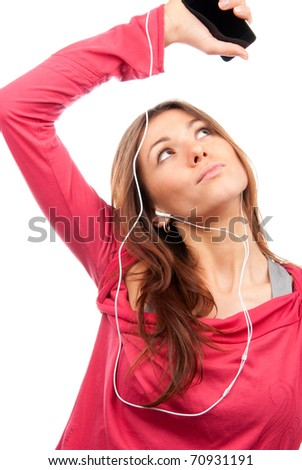 Pretty young woman listening and enjoying music on her new cellular touch mp3 player in headphones wearing dance pink top, isolated on white background - stock photo