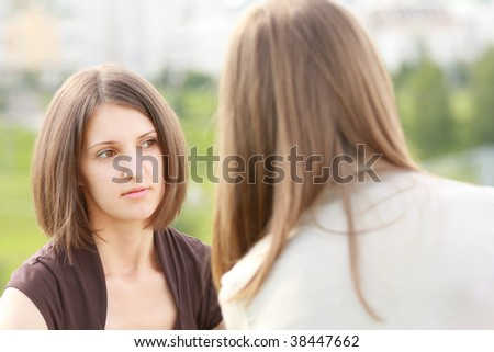 Pretty young woman listening friend seriously outdoors - stock photo