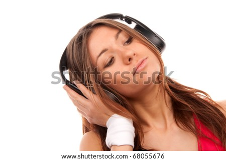 Pretty young woman listening music on her new cellular touch mp3 player in big headphones wearing dance pink top, isolated on white background - stock photo