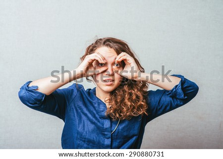 Pretty young woman looking for something with wide open eyes and imaginary binocular - stock photo