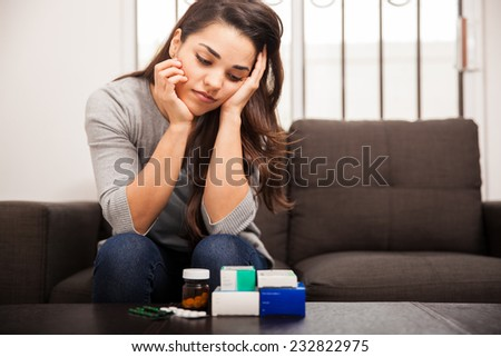 Pretty young woman looking overwhelmed while gazing at too many medicines at home - stock photo
