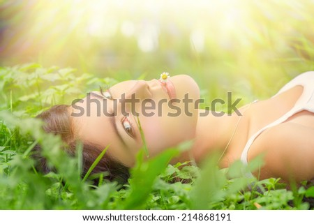 pretty young woman lying in grass under sun rays
