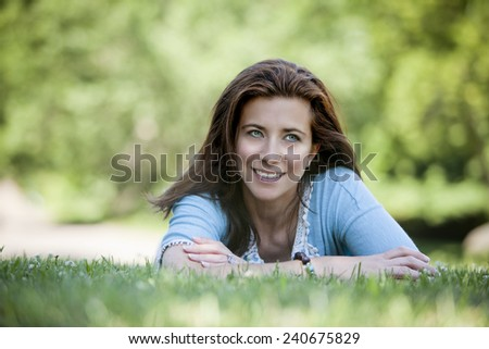 Pretty young woman lying on grass in summertime - stock photo