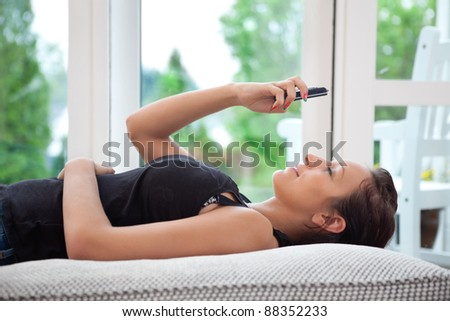 Pretty young woman lying on sofa using cell phone - stock photo