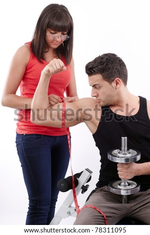 Pretty young woman measuring the biceps of handsome muscular man