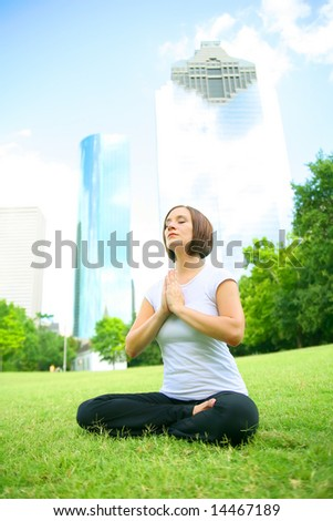 pretty young woman meditate outdoor in a park with downtown building on the background. concept for yoga or wellbeing - stock photo