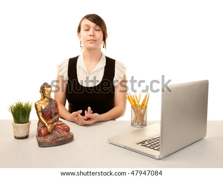 Pretty young woman meditating at her desk - stock photo