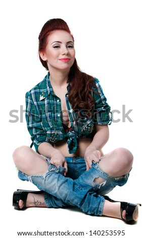 Pretty young woman model with long legs, wearing green checked shirt, ripped blue jeans, black high heels, red hairstyle, sitting on floor, legs crossed, smiling, looking at camera. Isolated on white - stock photo