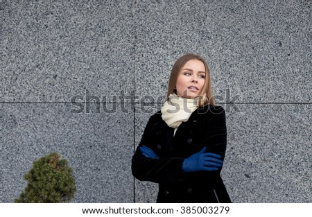 Pretty young woman on a gray background in the street in autumn - stock photo