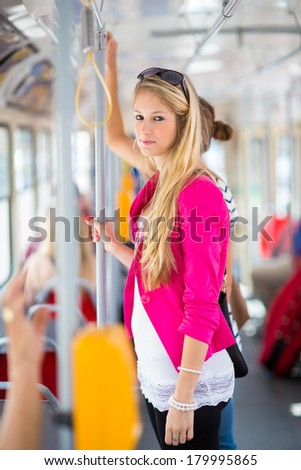 Pretty, young woman on a streetcar/tramway, during her commute to work (color toned image; shallow DOF) - stock photo