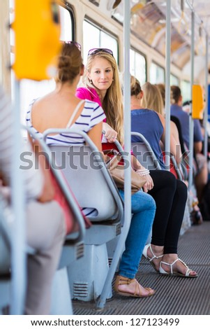 Pretty, young woman on a streetcar/tramway, during her commute to work/school (color toned image; shallow DOF) - stock photo