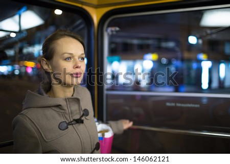 Pretty, young woman on a streetcar/tramway, during her evening commute home from work (color toned image; shallow DOF) - stock photo