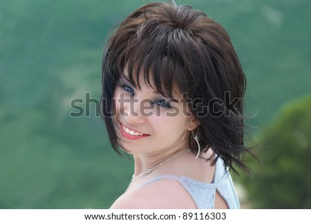 Pretty young woman on the field with green grass - stock photo