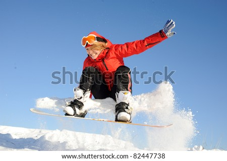pretty young woman on the snowboard jumping over the slope in winter - stock photo
