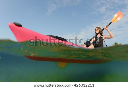 Pretty young woman paddling a kayak in tropical location in the ocean - stock photo