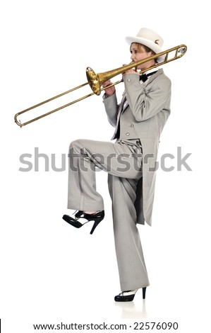 Pretty young woman playing a trombone while wearing tuxedo and top hat.