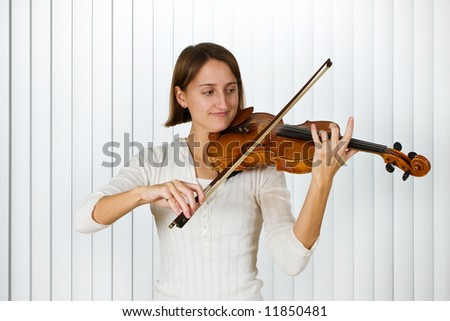 Pretty young woman playing the violin. - stock photo