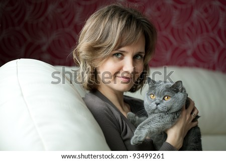 Pretty young woman playing with a gray cat British breed - stock photo