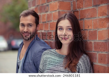 Pretty young woman posing against a brick wall with her husband alongside her looking at the camera with a friendly sincere smile, focus to the wife - stock photo
