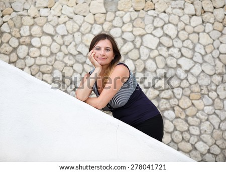 Pretty young woman posing, leaning on the parapet on the background of old stone vintage wall. Selective focus on model. Photo in retro style. - stock photo