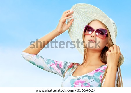 Pretty young woman posing over blue sky. - stock photo