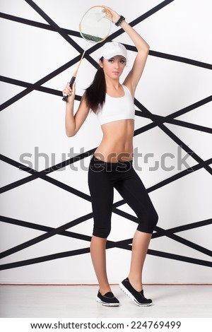 Pretty young woman posing with badminton racket - stock photo