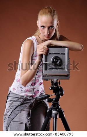 Pretty young woman posing with large format camera - stock photo