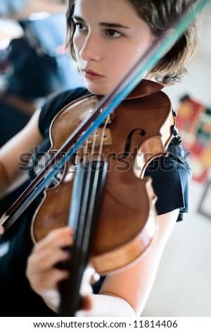 Pretty young woman practicing her violin with total concentration; soft focus - stock photo