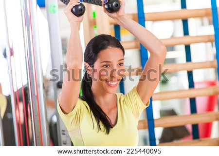Pretty young woman practicing in the gym. A young woman in a health club