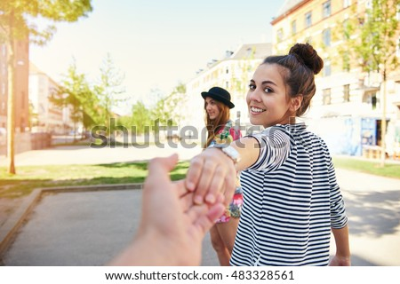 Pretty young woman pulling a man along by the hand turning to look back at him with a happy smile as her friend waits in the background