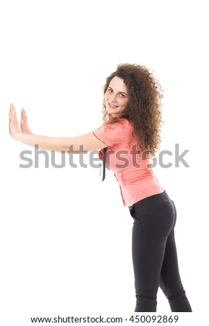 Pretty young woman pushing something imaginary isolated over white background - stock photo