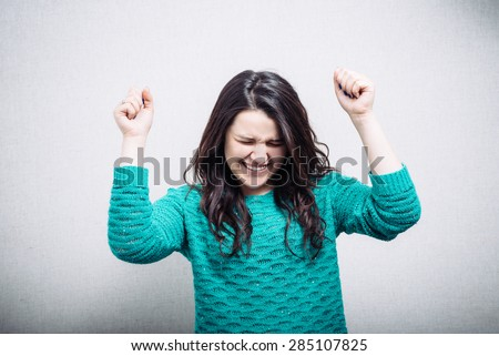 pretty young woman raising a fist in celebration, triumph, excitement - stock photo