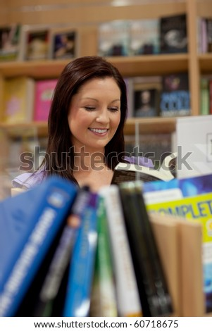 Pretty young woman reading a book in a bookstore - stock photo