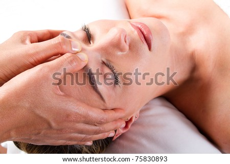 pretty young woman receiving a head massage in beauty salon