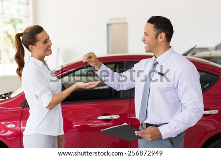 pretty young woman receiving car key from dealership - stock photo