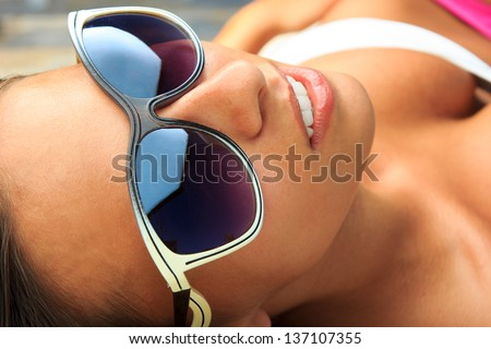 Pretty young woman relaxed by the pool in her bikini on a summers day - stock photo