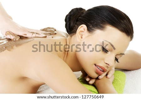 Pretty young woman relaxing being massaged in spa saloon with chocolate. Isolated on white - stock photo