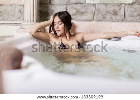 Pretty young woman relaxing in the hot tub - stock photo