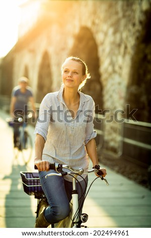 Pretty, young woman riding a bicycle in a city with her boyfriend (color toned image; shallow DOF) - stock photo