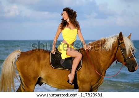 Pretty young woman riding a horse on the beach - stock photo