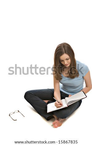 Pretty young woman seated on floor writes in a notebook - stock photo
