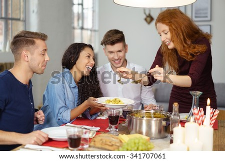 Pretty Young Woman Serving Appetizing Food to her Friends Wile Having Dinner.