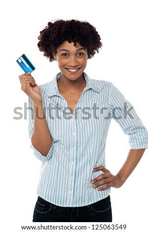 Pretty young woman showing credit card to the camera.