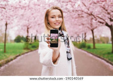Pretty young woman showing picture of spring blossom garden while standing at a park. Caucasian young female showing spring park picture on her mobile phone. - stock photo