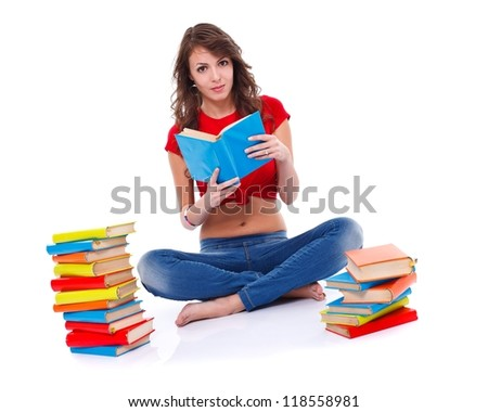Pretty young woman sitting among books and reading