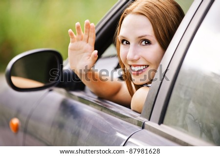 pretty young woman sitting car looking out window waving smiling - stock photo